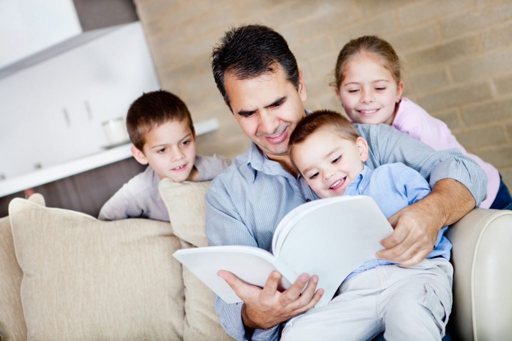 Father reading to three children on the couch