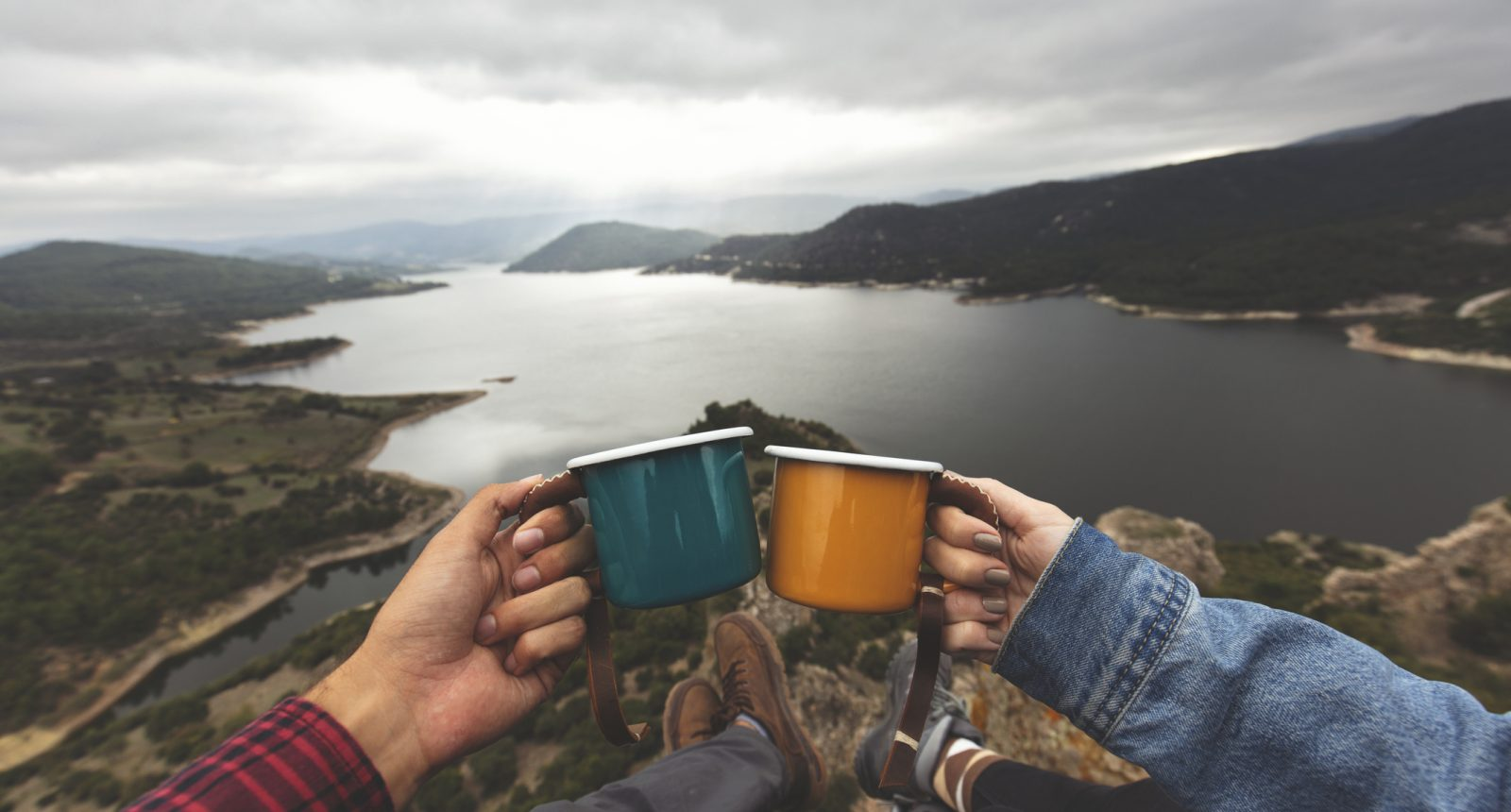 Pov image of couple holding cups on mountain peak