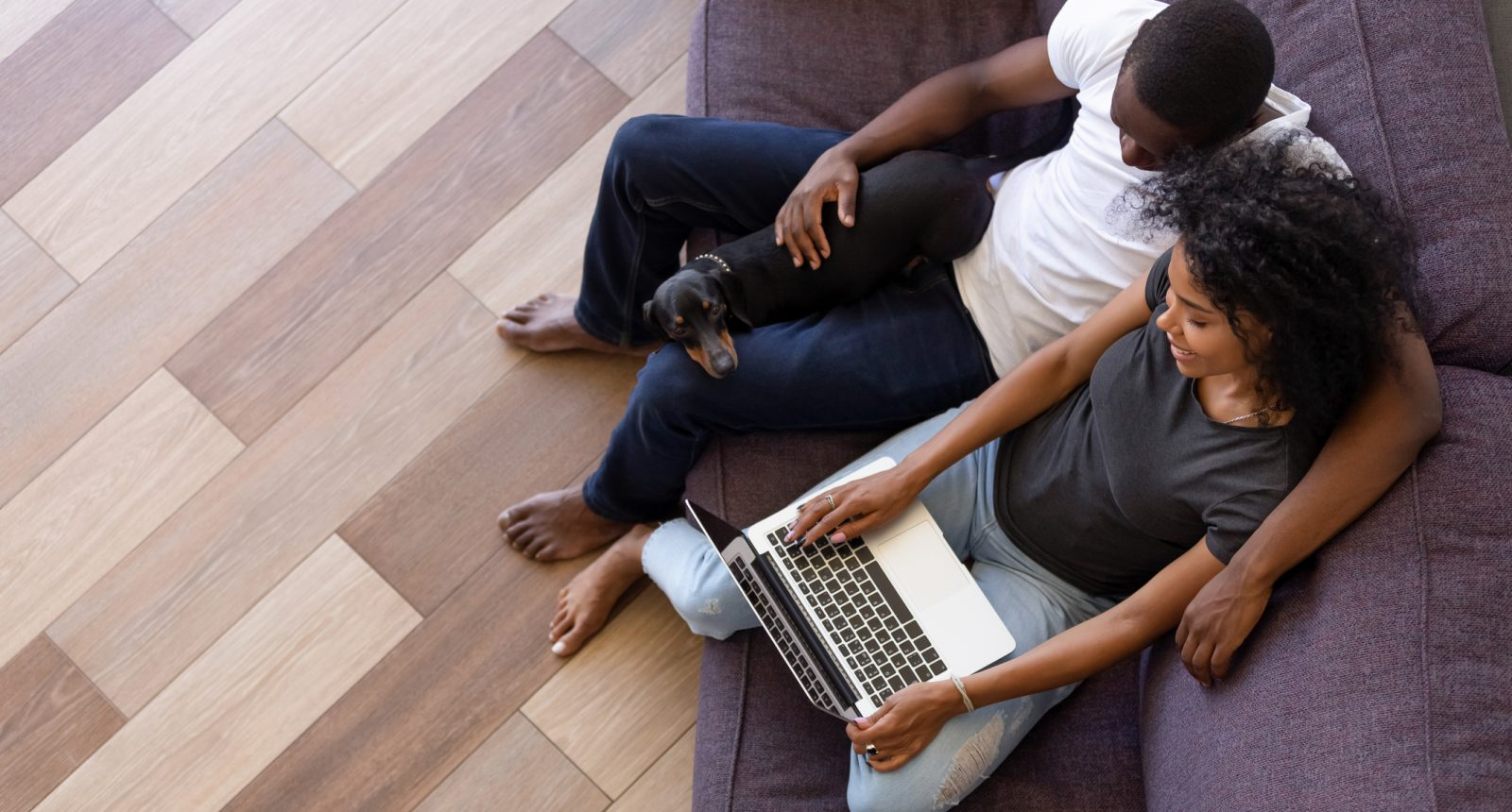 Couple cuddling on couch looking at laptop with dog on lap