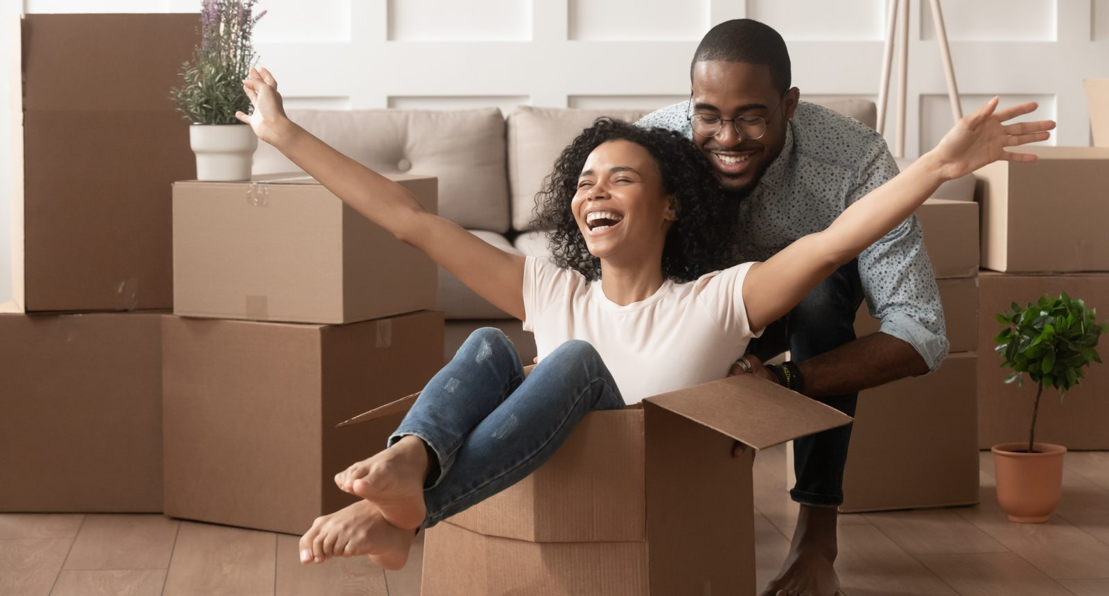 Man pushing woman in a box while moving in