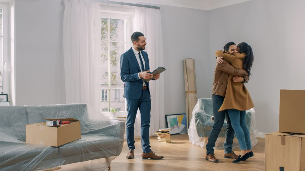Real Estate Agent smiling while couple embraces about their new home