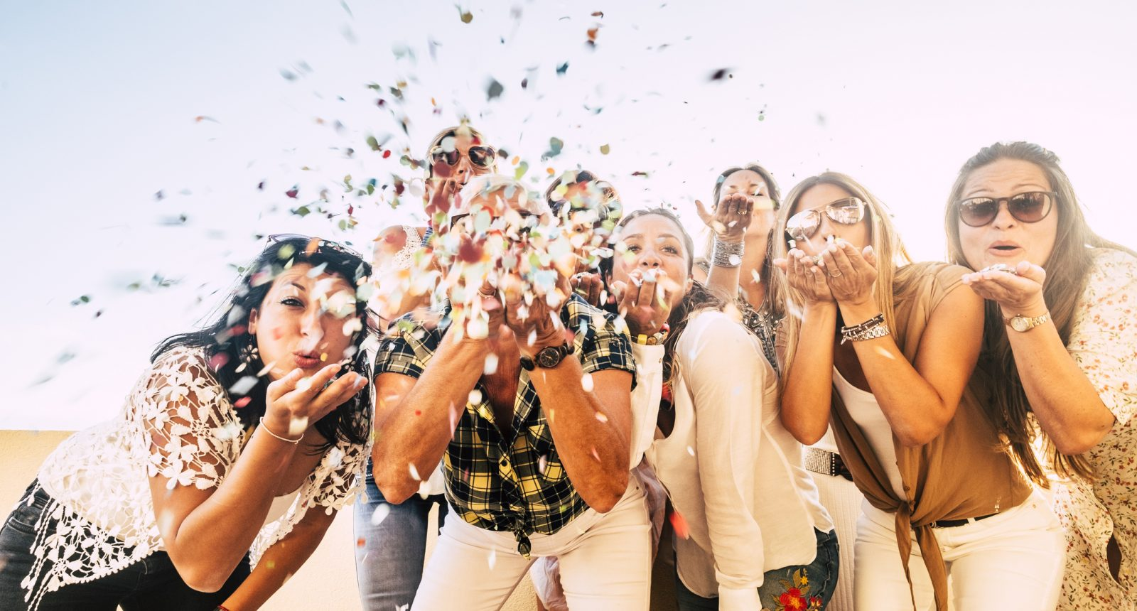 Group of women blowing confetti