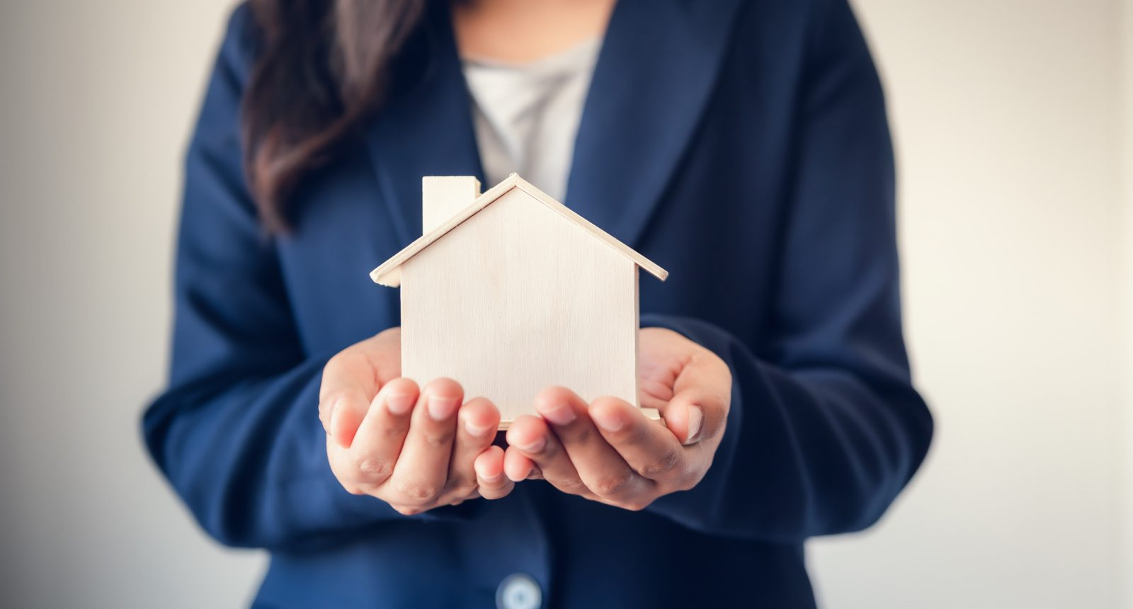 Women holding a miniature wood home in her hands