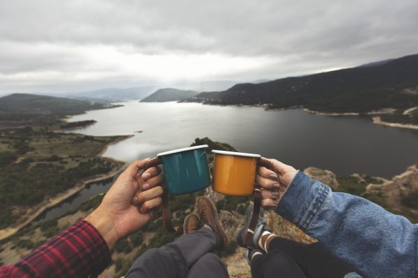 Couple drinking out of mugs on a hill